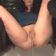 A brunette woman pisses and shits while spread-eagle over a bath tub.
